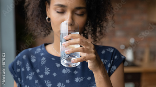 Obraz Close up satisfied African American young woman enjoying, drinking pure fresh mineral water with closed eyes, holding glass, healthy lifestyle and good daily habit concept, body and skin care - fototapety do salonu
