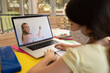 Female student wearing face mask having a video call with female teacher on laptop at school
