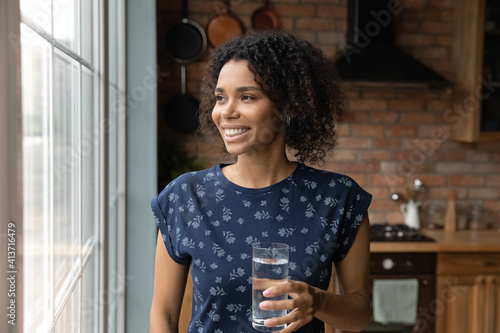 Close up dreamy smiling African American woman holding glass of pure fresh mineral water, standing near window in kitchen, starting new day, healthy lifestyle habit, body and skin care concept