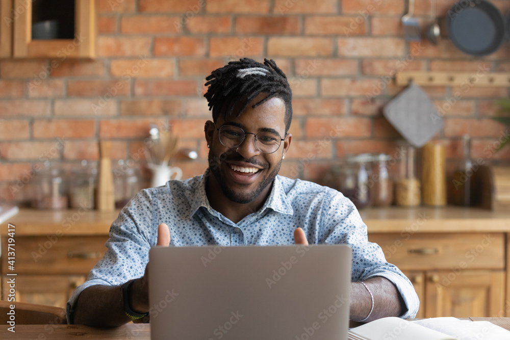 Fototapeta Close up smiling African American man wearing glasses using laptop, looking at screen, making video call, speaking, happy student involved in internet conference, webinar, studying at home in kitchen