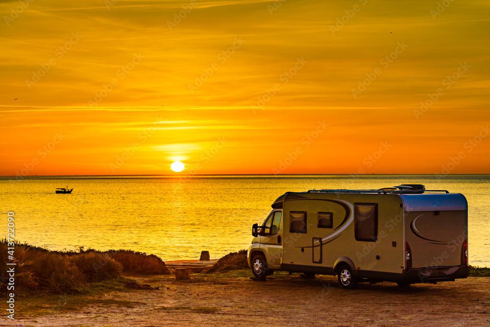 Fototapeta Camper vehicle on beach at sunrise