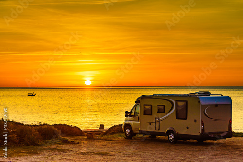 Fototapeta Camper vehicle on beach at sunrise obraz