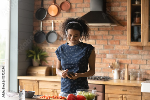 Obraz Smiling African American woman wearing headphones using phone, listening to music, enjoying leisure time, standing in kitchen, searching vegetarian snacks recipe or chatting, cooking salad at home - fototapety do salonu