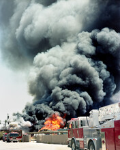 Fire Engines Against Smoke Emitting From Burning Crates In Factory