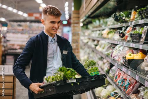 Fototapeta Shop assistant restocking the produce section shelves obraz