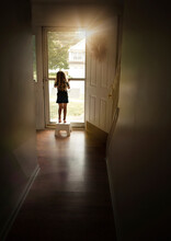 Rear View Of Girl Standing By Door At Home