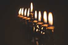 Close-up Of Hanukkah Menorah Candles Glowing In Darkroom