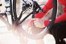 Midsection Of Athlete Examining Bicycle During Sunny Day
