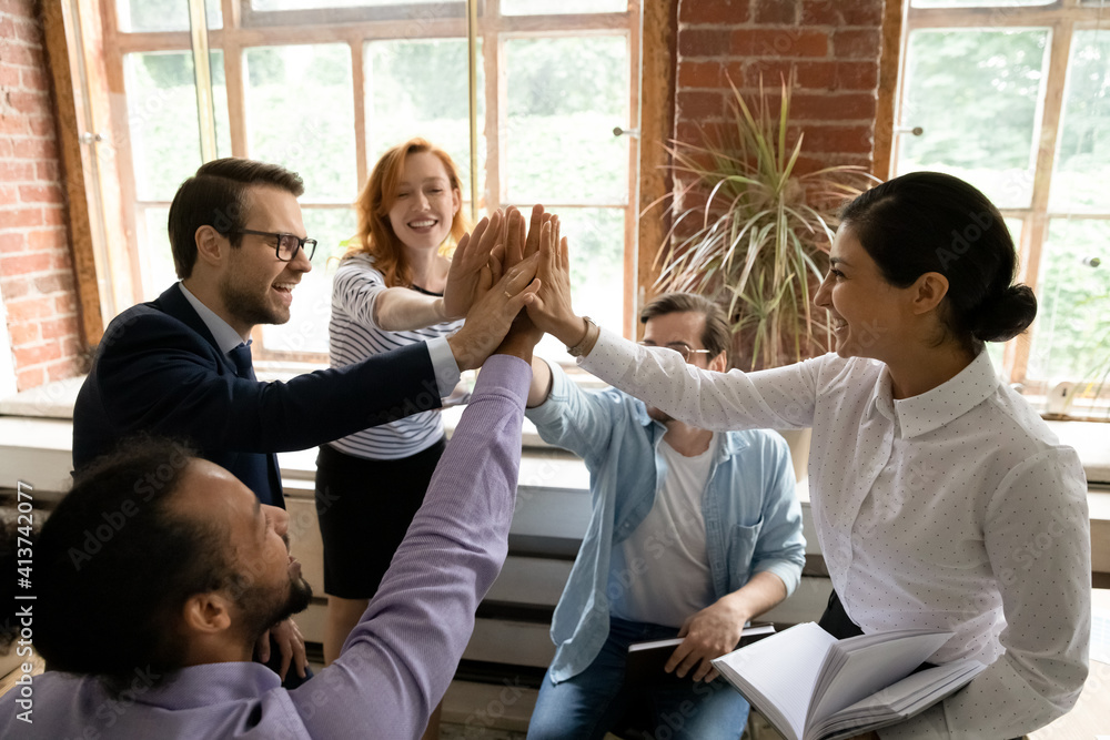 Fototapeta Excited diverse multiracial businesspeople give high five engaged in teambuilding activity at team office meeting. Happy multiethnic colleagues celebrate work result at briefing. Teamwork concept. - obraz na płótnie