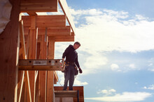Worker Standing On Wooden Frame Against Sky During Sunny Day