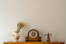 Still Life Of Antique Clock With Floral Jug And Optical Prescription Glasses On Stand