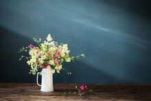 Wild Flowers In White Jug On Dark Background