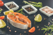 Fresh Raw Salmon Steak On Blackstone Cutting Board With Salt, Peppers, Lime, And Rosemary, Close Up