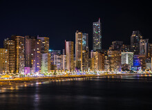 Night Skyline Of Benidorm With Many Lights From The Skyscrapers Lighting The Beach, The Coast And The Mediterranean Sea When Arrives O The Shore. Horizontal Picture