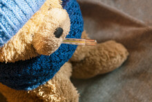 Plush Bear With Thermometer In Mouth. Wearing Knitted Hat And Scarf. Cold, Flu, Illness, High Temperature Concept