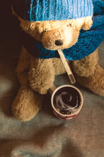 Plush Bear With Cup Of Hot Coffee With Thermometer In Mouth. Wearing Knitted Hat And Scarf. Cold, Flu, Illness, High Temperature Concept