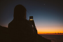 Rear View Of Woman Photographing Sunset Through Smart Phone
