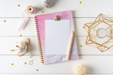 Top View Of White Working Table Background With Blank Paper Notebook, Nature Cotton. Flat Lay Still Life Candle, Golden Paper Binder Clips. Notepad And Pen. Desktop Mockup, Workspace, Stationery.