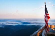 American Flag On Railing Of Fire Lookout Tower Against Landscape