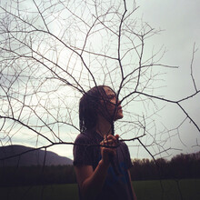 Boy Looking Away While Holding Bare Branches On Field Against Sky