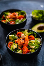 Salmon Salad - Smoked Salmon With Avocado And Mix Of Vegetables On Black Wooden Table