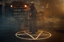 Male Exorcist In Hood Standing In The Magic Circle