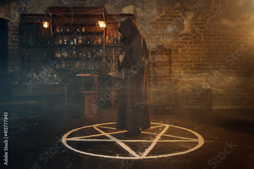 Canvas Print Male exorcist in hood standing in the magic circle