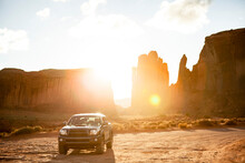 Off-road Vehicle Parked Against Rock Formations At Monument Valley During Sunny Day