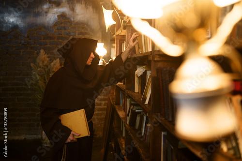 Obraz na plátne Exorcist in black hood choosing book of spells