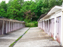 Garages With Metal Gates On Both Sides Of The Concrete Floor And Green Leafy Forest Behind The Fence. Garage Sector