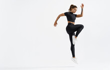 Fit Woman Exercising Indoors. Healthy Young Female Athlete Doing Fitness Workout. Sportswoman In Sport Clothing Jumping On White Background, Training Muscles Before Running