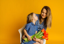 Daughter In A Blue Dress With Red Tulips Kisses Her Mother On A Yellow Background. Mother's Day