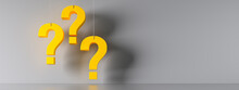 Three Yellow Question Marks In Front Of A Gray Wall