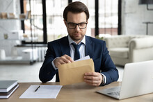 Young Caucasian Businessman Sit At Desk In Office Open Envelope With Post Paper Letter Or Correspondence. Focused Male CEO Or Boss Receive Postal Paperwork Or Mail, Consider Message Or Notice.