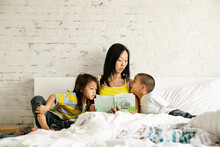 Mother Reading Book To Children While Sitting On Bed Against Wall At Home