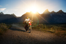 Man Riding Motorcycle On Dirt Road Against Mountains