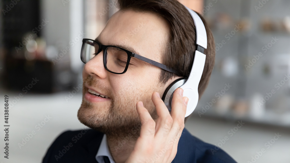 Fototapeta Close up of calm happy young Caucasian businessman wear headphones enjoy good quality sound on gadget. Smiling male boss or CEO relax rest listen to music in earphones in office. Technology concept.
