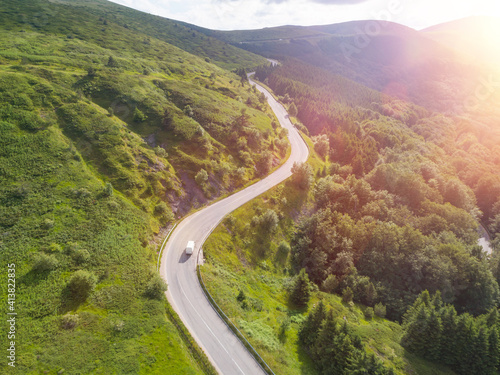 Fotografija Drone following truck on winding mountain passage road