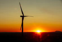 Wind Turbines In A Field With Clear Sky At Sunset
