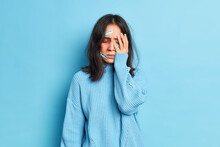 Desperate Woman Covers Face With Hand Has Bruise Being Victim Of Family Violence Beaten By Cruel Husband Dressed In Casual Sweater Isolated Over Blue Background. Injured Abused Sorrowful Female