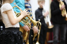 A Group Of Children Students Young Musicians Boys And Girls With Musical Instruments Trumpet Standing In A Row In The Classroom Listening Attentively.The Concept Of School Music Education