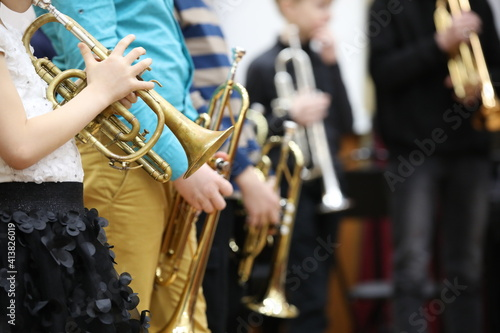 Obraz na płótnie A group of children students of young musicians boys and girls with musical instruments trumpet and saxophone at a music lesson in the classroom