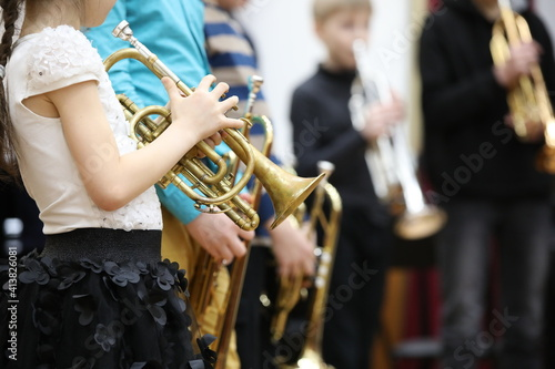 A group of children students young musicians boys and girls with musical instruments trumpet standing in a row in the classroom listening attentively Fototapet