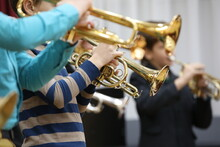 A Group Of School Musicians Plays Wind Instruments A Golden Shiny Trumpet A Flugelhorn While Rehearsing Indoors