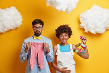 Diverse Couple Expect Baby Pose With Toys And Clothes For Child Going To Become Parents. Happy Pregnant Womann Holds Belly And Mobile. Shocked Future Father Prepares Bodysuit Fot Infant. Parenthood