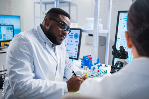 Fototapeta Professional team of scientists is working on a vaccine in a modern scientific research laboratory. Genetic engineer workplace. Future technology and science. obraz