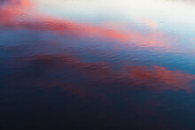 Pink Orange And Blue Contrast Reflection Of Sunset On Rippled Water