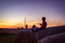 Small Boy Watching The Sunset While Sitting On A Hay Bale
