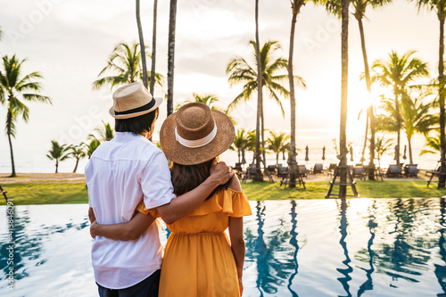 Obraz Young couple traveler relaxing and enjoying the sunset by a tropical resort pool while traveling for summer vacation - fototapety do salonu