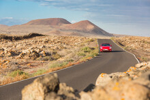 Red Cabrio Car Driving Empty Paved Road In Desert Volcanic Landscape